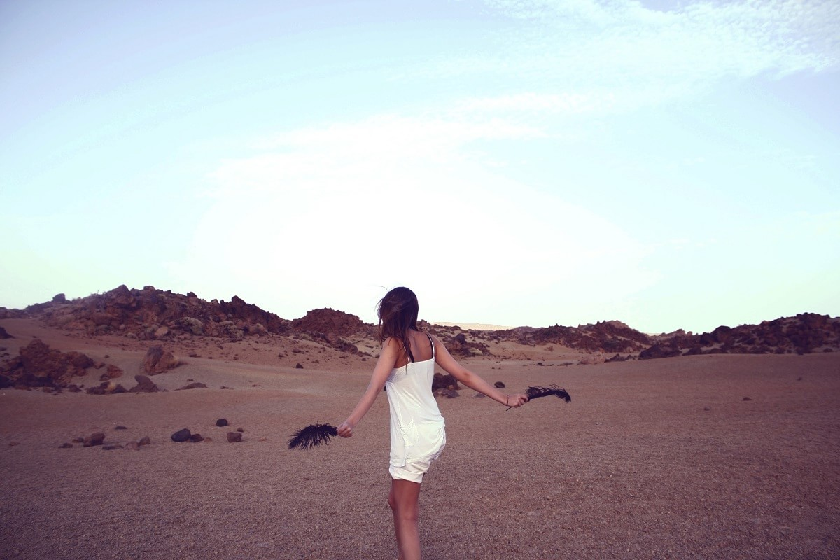 Woman walking in dessert holding feathers